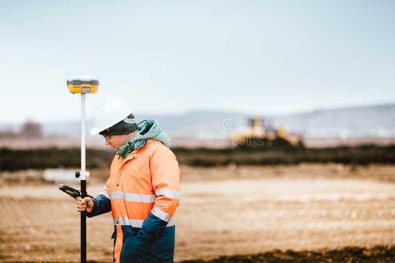 Landmetersingenieur die met technologie voor het coördineren op zwaar werk berekende machines werken stock foto