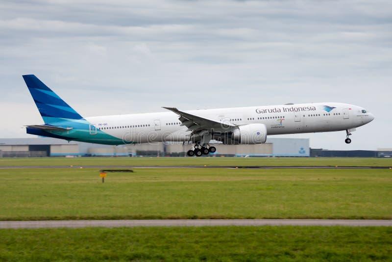 Landning för Garuda Indonesia Boeing 777-300ER PK-GIC passagerarenivå på den Amsterdam Schipol flygplatsen fotografering för bildbyråer