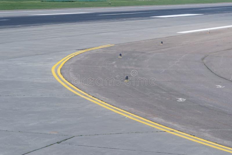 Landningsbanakurva på flygplatsen med den gula dubbla linjen royaltyfri foto