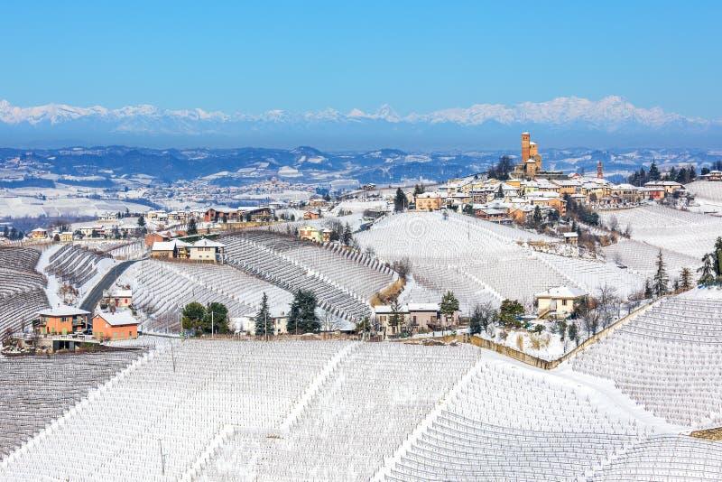Landsbygdshus och mindre stad på snötäckta kullar fotografering för bildbyråer
