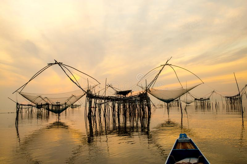 Landscape Amazing giant fish lift net in Phatthalung,Thailand. Landscape view  giant fish lift net with sunrise and golden sky reflection in canal during travel royalty free stock photography