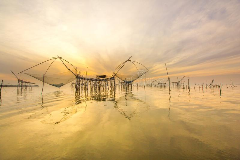 Landscape Amazing giant fish lift net in Phatthalung,Thailand. Landscape view  giant fish lift net with sunrise and golden sky reflection in canal during travel royalty free stock photo