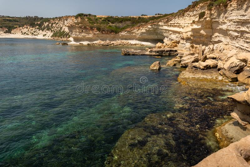 Landscape Around Marsascala Malta. Cliffs, arch, crystal clear Mediterranean water around st thomas bay. side and above view. Serenity, tranquility. while royalty free stock images