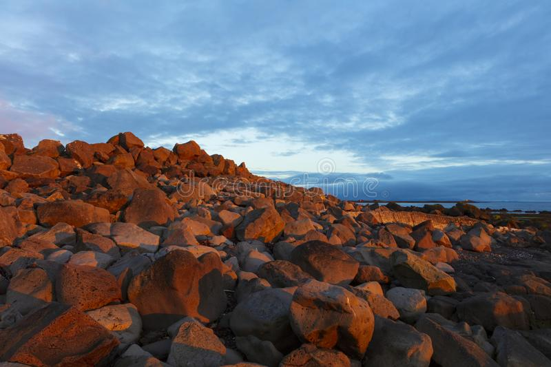 A landscape around sunset of the Atlantic Coast, photographed near the Grotta Island Lighthouse, Reykjavik, Iceland. A rocky coast illuminated by a sunset along royalty free stock photography