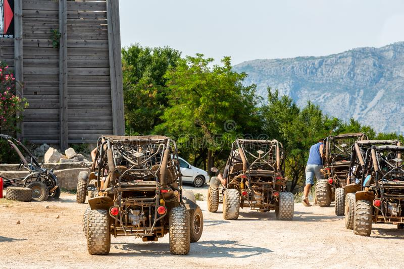 Landscape back view of several dune buggy vehicles and incidental people. stock photos