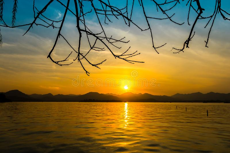 The landscape Background of a golden sunset reflect water and silhouette mountain in west lake xihu in Hangzhou CHINA - Image royalty free stock photography