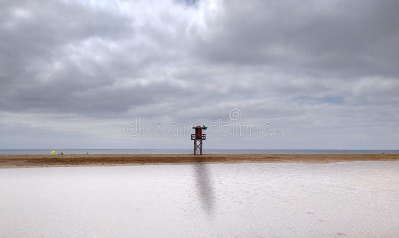 landscape of a beach with cloudy sky and a tall lifeguard station with green flag at the middle. At first the sea water has royalty free stock photo
