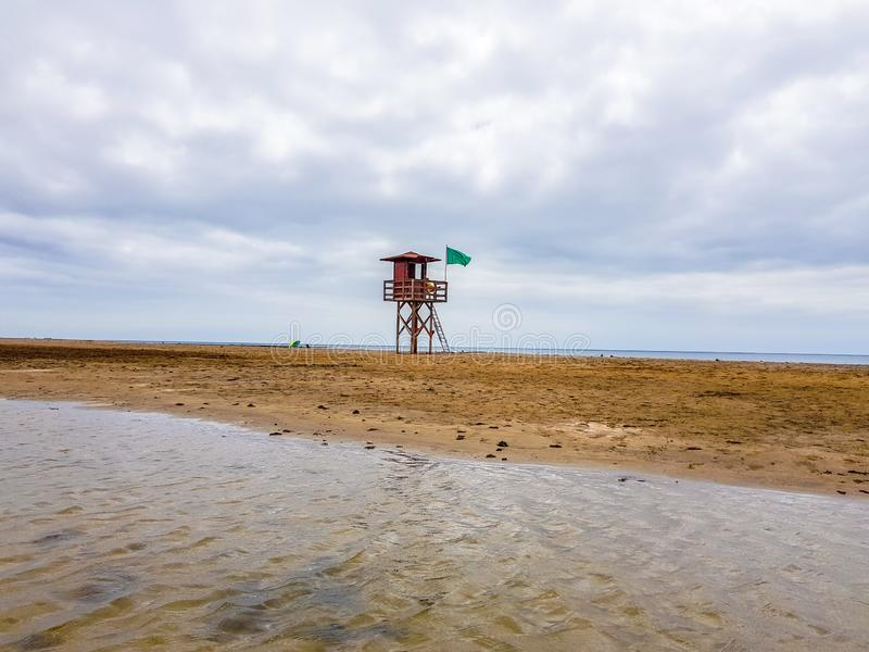 Landscape of beach and sea with lifeguard post and green vandera allowing the bath. Canary Islands, Spain. Water tracks morning wet sky surf nature tropical stock photos