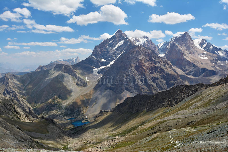 Landscape of beautiful high Fan mountains and Alaudin�lake in Tajikistan. On blue cloudy sky background royalty free stock photography