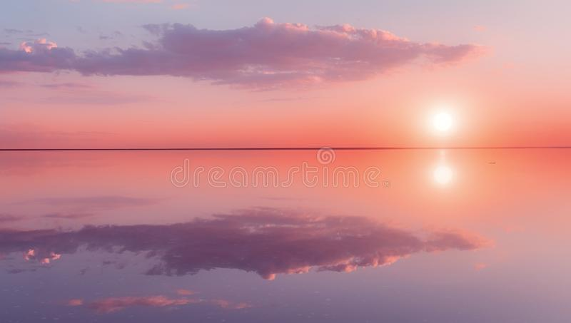 Landscape beautiful lilac sunset red sky solt lake saline Elton Baskunchak. The sun sets behind the horizon. The clouds. Are like the hands of a man holding the stock image