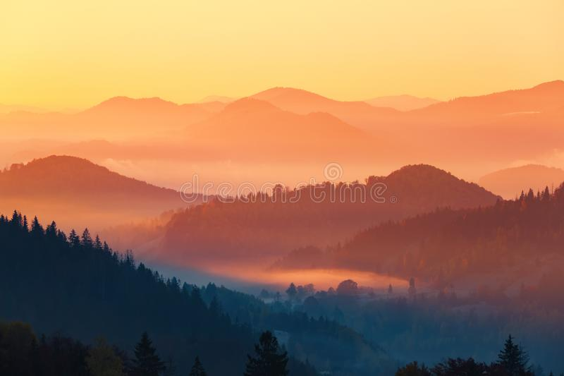 Landscape with beautiful mountains, fields and forests covered with thick morning fog. Interesting sunrise enlightens surroundings royalty free stock photos
