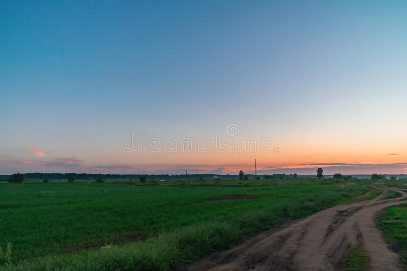Landscape beautiful summer orange sunset over green field with rural dirt road. Clear blue sky with sunset lighting. royalty free stock photo