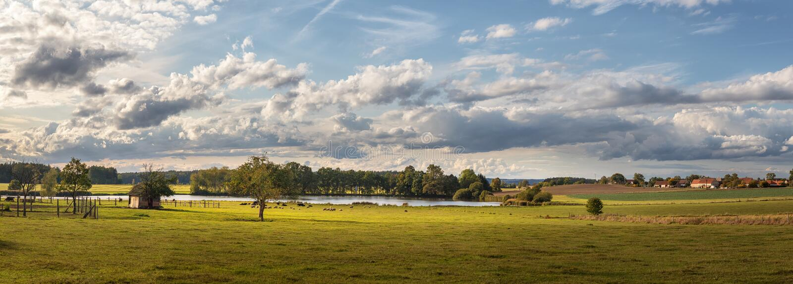 Landscape with blue sky and clouds - panorama of rural countryside with pond royalty free stock photo