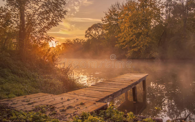 Landscape.bridge frost wooden on the shore of river in the morning mist. late fall. stock photos
