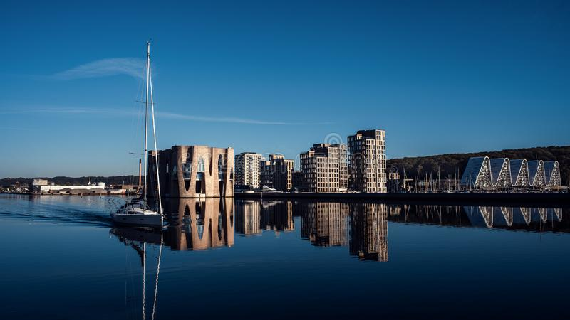 Landscape of buildings near the pier. Yacht on the background of new buildings. Blue color. stock photography