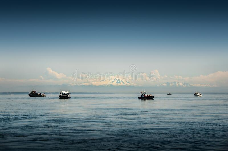 Landscape with calm ocean, blue sky and snow mountains on the horizon. Whale watching boats in the foreground, Vancouver. Dreamstime royalty free stock photos