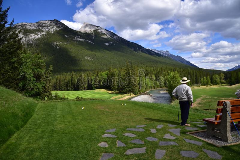 An unidentified man is playing golf in middle of amazing landscapes. A landscape of Canadian Rocky Mountain with a view of golf ground in Banff National Park royalty free stock image