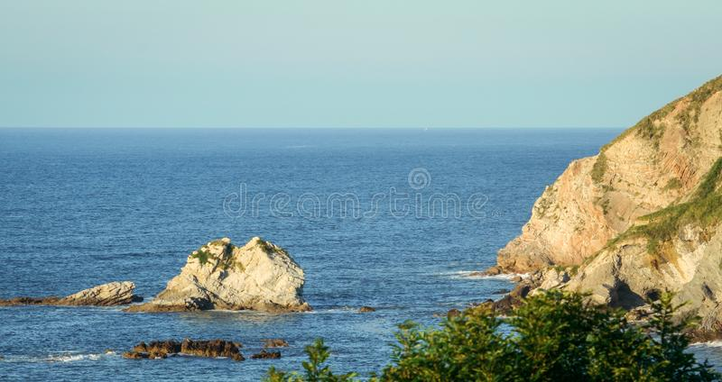 Cantabrian Sea, cliffs rising from the sea. Landscape of the Cantabrian Sea, mountains and rocks that are born in the water and a blue sky in the background stock photos