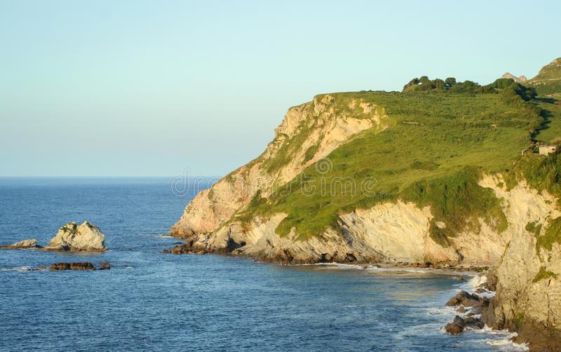 Cantabrian Sea, cliffs rising from the sea. Landscape of the Cantabrian Sea, mountains and rocks that are born in the water and a blue sky in the background royalty free stock photo