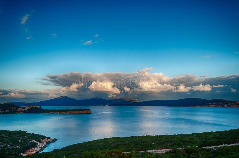 Landscape of capo caccia gulf. Under a dramatic sky after the storm at sunset, alghero, italy, adventure, bay, beach, beautiful, blue, capocaccia, coast royalty free stock photos