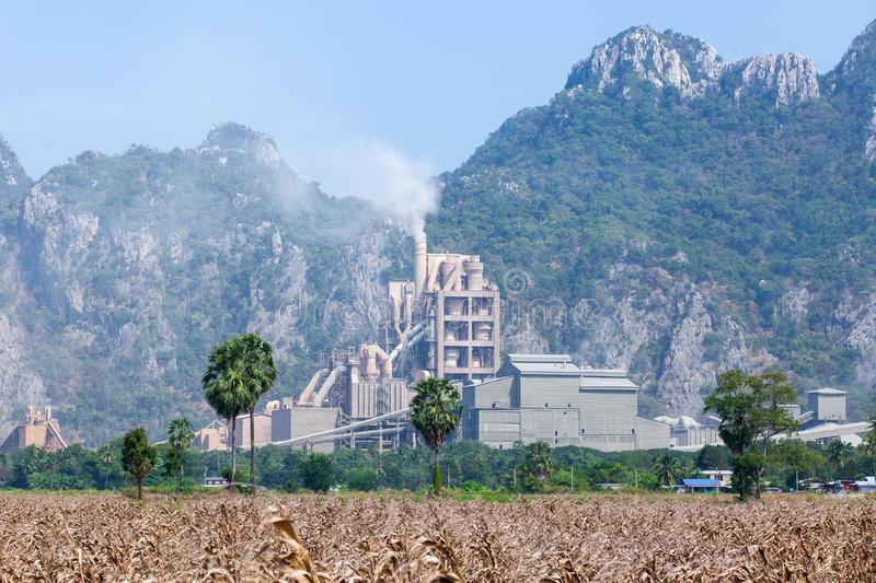 Landscape of cement factory in thailand, corn fields foregrounds, limestone mountain range backgrounds stock photo