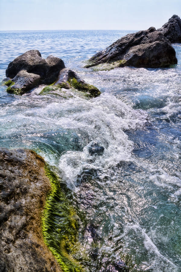 Landscape with coast stones in sea waves royalty free stock images