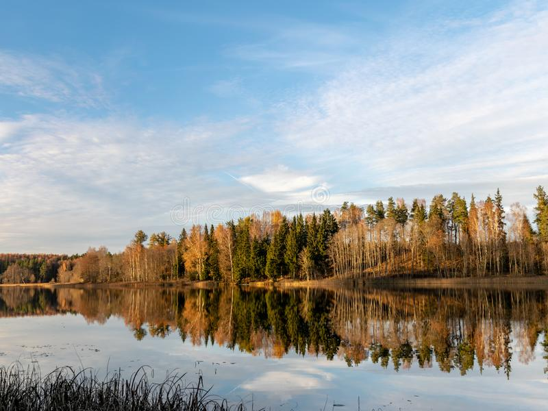 Landscape with colorful trees on the water`s edge and wonderful reflections on the water, beautiful autumn day stock images