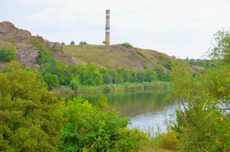 The landscape consists of a picturesque pond, rocks and a concrete pipe enterprise. royalty free stock photo