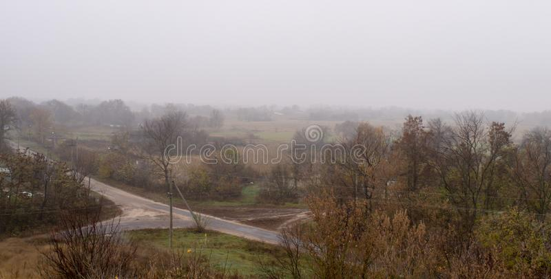 Landscape with cross street at foggy forest background on a cloudy day. In golden autumn stock images