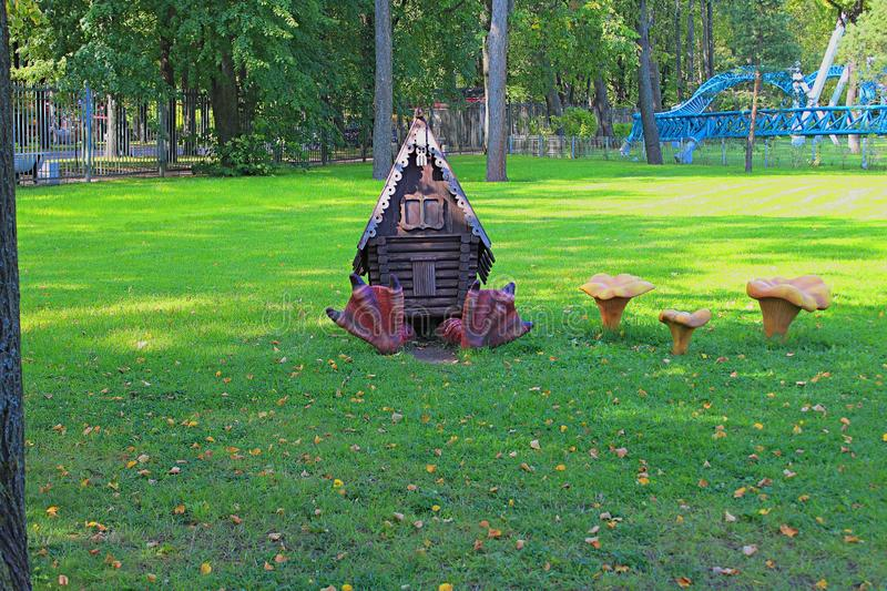 Landscape design,fabulous hut on chicken legs and mushrooms chanterelles on the green lawn stock photography