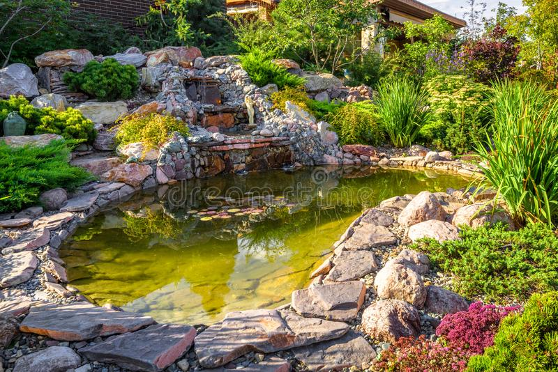Landscape design of home garden close-up. Beautiful landscaping with small pond and waterfall. Landscaped place with rocks at country house. Stone landscaping royalty free stock photography