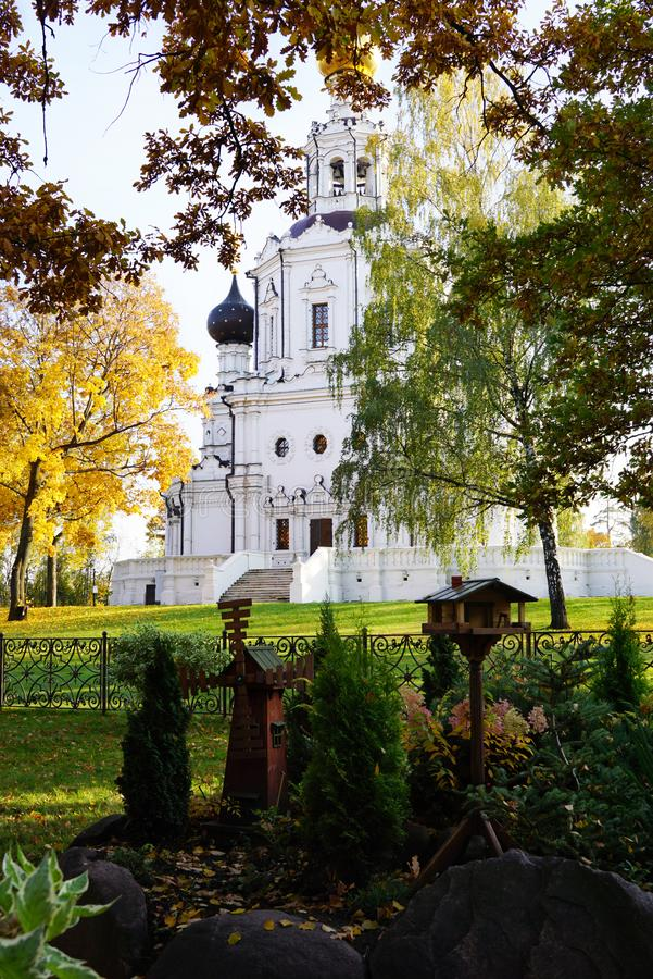 Old Orthodox church with a cross through the autumn foliage. Mos. Landscape design in the style of a small park with a mill and a house, decorated with large stock photography