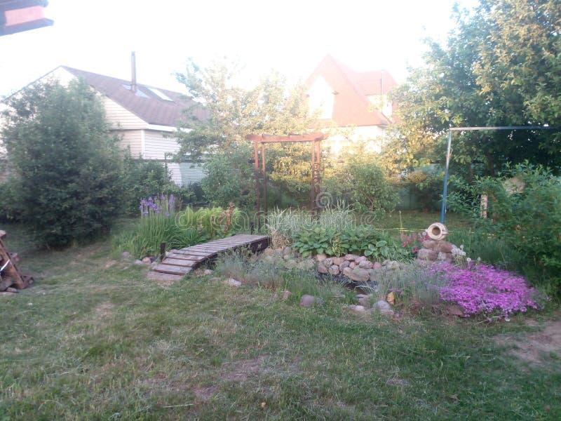Landscape design: wooden bridge, arch, pond, jug and purple flowers at the village. Landscape design: wooden bridge, arch, pond, jug and purple flowers at the stock images