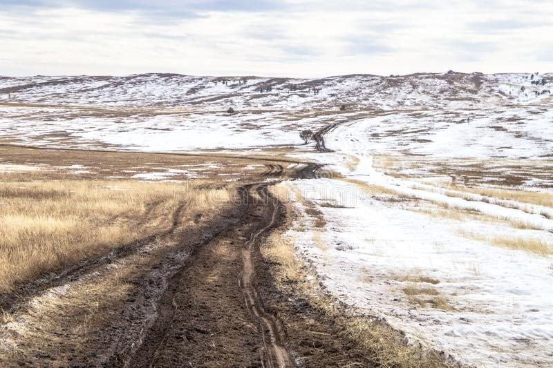 The landscape with the dirt road, dried grass and snow covered land in the steppe. This photo was taken in March on Olkhon island royalty free stock photo