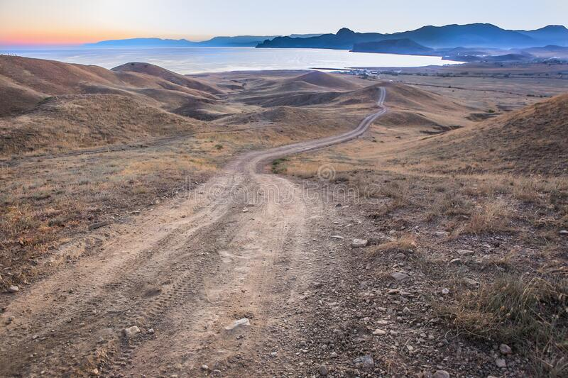 Landscape dirt road over the hills to the sea royalty free stock image