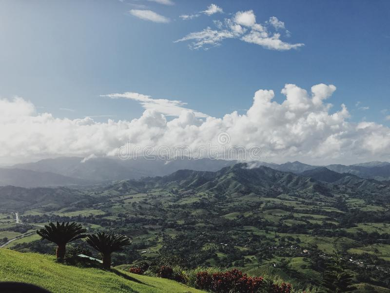 Landscape of Dominican mountains under cloudy sky view from Redonda mountain. Green hills, blue sky, huge white clouds, sunlight spots on the grass, palm trees stock photos