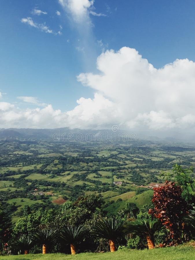 Landscape of Dominican mountains under cloudy sky view from Redonda mountain. Green hills, blue sky, huge white clouds, sunlight spots on the grass, palm trees stock image