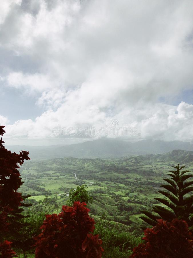 Landscape of Dominican mountains under cloudy sky view from Redonda mountain. Green hills, blue sky, huge white clouds, sunlight spots on the grass, palm trees royalty free stock image