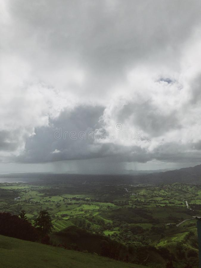 Landscape of Dominican mountains under cloudy sky view from Redonda mountain. Green hills, blue sky, huge white clouds, sunlight spots on the grass, palm trees stock photography