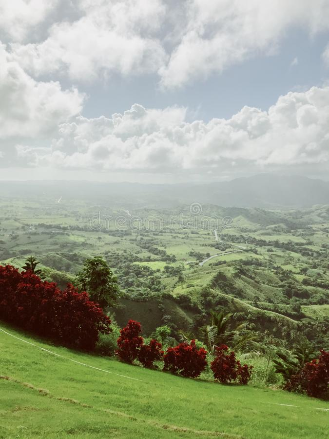 Landscape of Dominican mountains under cloudy sky view from Redonda mountain. Green hills, blue sky, huge white clouds, sunlight spots on the grass, palm trees royalty free stock photo