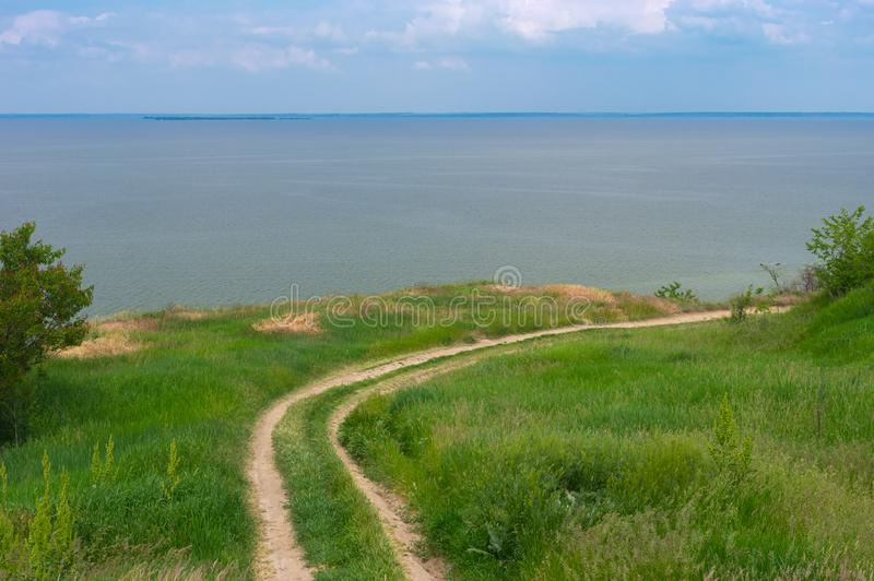 Landscape with an earth road leading to Kakhovka Reservoir located on the Dnipro river, Ukraine. Spring landscape with an earth road leading to Kakhovka stock photos