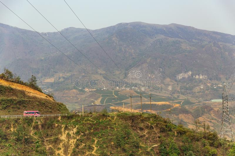 Landscape with electric posts and trees with pink color bus on the left side in summer in Sa Pa, Vietnam royalty free stock photo
