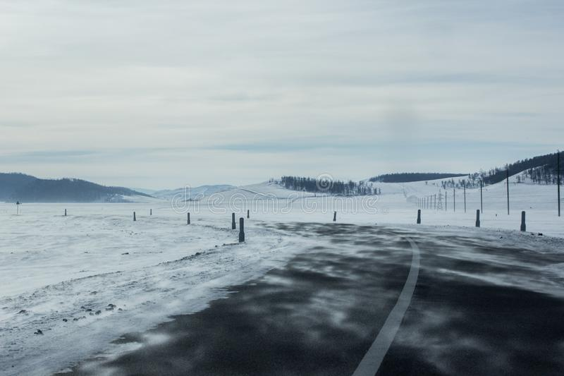 Landscape of empty asphalt road turn left through snow field and hill stock photos