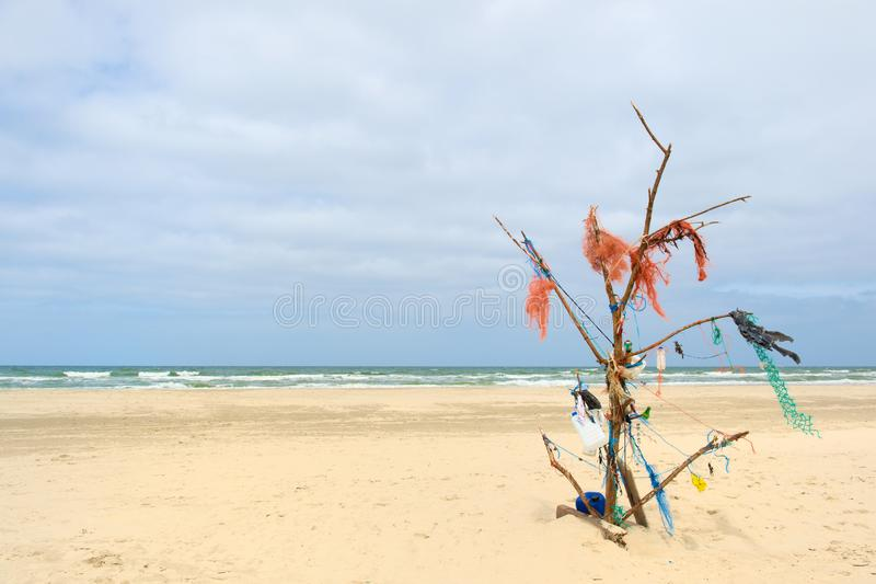 Landscape empty beach with rubbish tree. Landscape empty beach with tree made from rubbish at Dutch island Terschelling stock photos