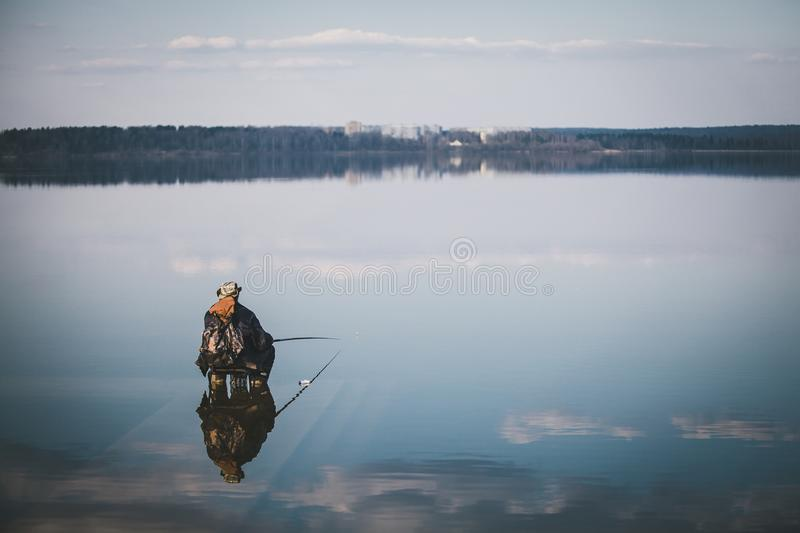 Landscape with a fisherman on the lake royalty free stock photography
