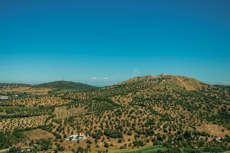 Landscape with fortress of on top of hill and small farms stock photography