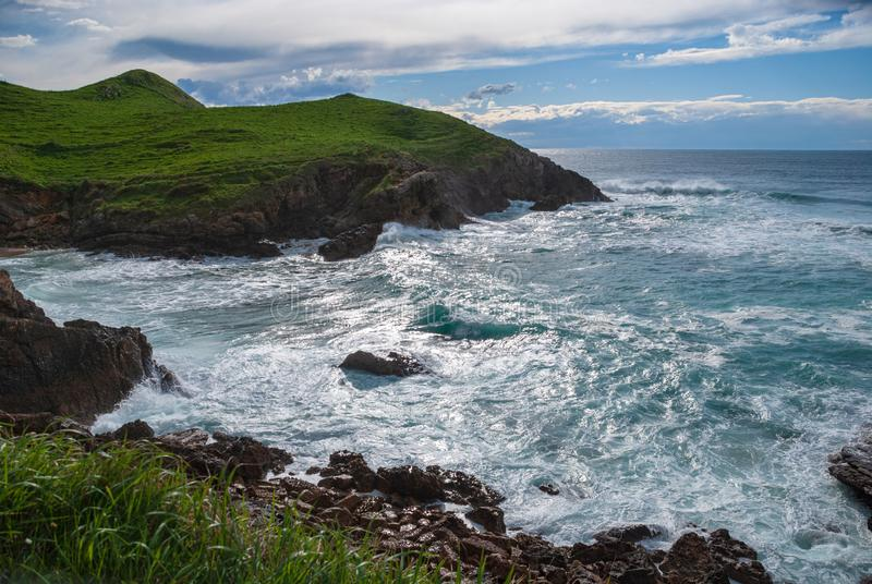 Landscape of green coast with rough sea. In the afternoon in Cantabria, Spain, Europe royalty free stock photo