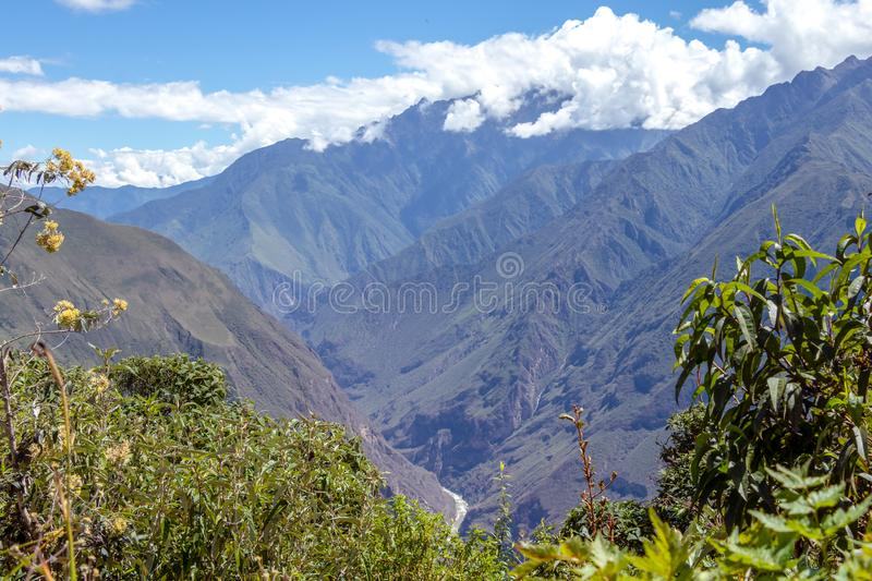 Landscape with green deep valley, Apurimac River canyon, Peruvian Andes mountains on Choquequirao trek in Peru. Apurimac River in green deep valley with white royalty free stock photography