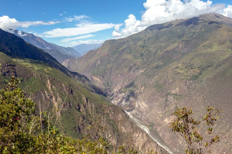Landscape with green deep valley, Apurimac River canyon, Peruvian Andes mountains on Choquequirao trek in Peru. Apurimac River in green deep valley with white royalty free stock photos