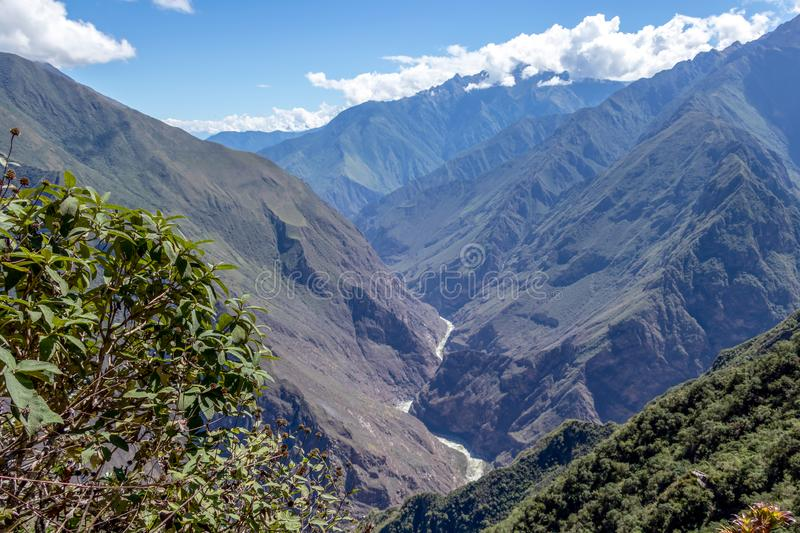 Landscape with green deep valley, Apurimac River canyon, Peruvian Andes mountains on Choquequirao trek in Peru. Apurimac River in green deep valley with white stock image